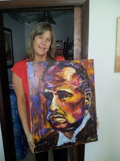 Katey Penner holding one of her iconic portraits